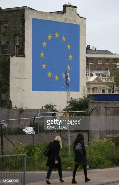 Pedestrians walk past a recently painted mural by British graffiti artist Banksy depicting a workman chipping away at one of the stars on a European...