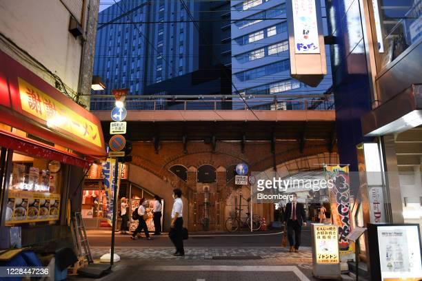 Pedestrians walk past a restaurant built under railway tracks, back, near Yurakucho station in Tokyo, Japan, on Thursday, Sept. 3, 2020. In Tokyo,...