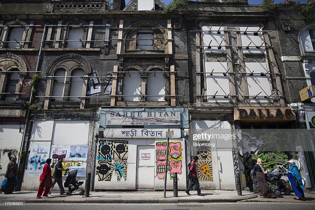 Pedestrians walk past a row of closed down stores in a derelict building in London, U.K., on Monday, July 8, 2013. Britain's economy could be in line for a period of 'strong catch-up growth' once it gets through the current weakness, according to Capital Economics Ltd. Photographer: Simon Dawson/Bloomberg via Getty Images