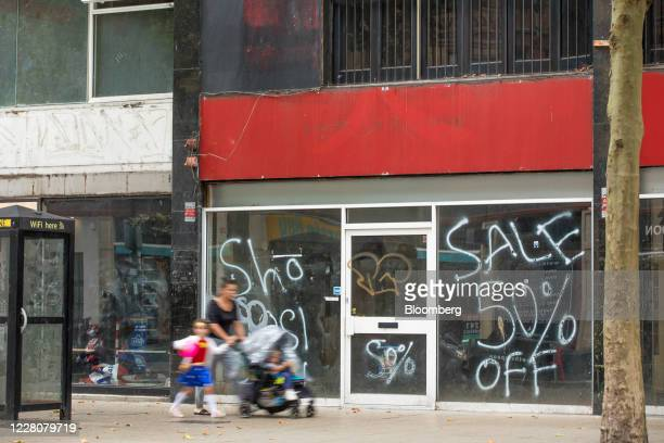 Pedestrians walk past a row of closed shops in Croydon, Greater London, U.K., on Monday, Aug. 17, 2020. The relief as economic activity surged in...
