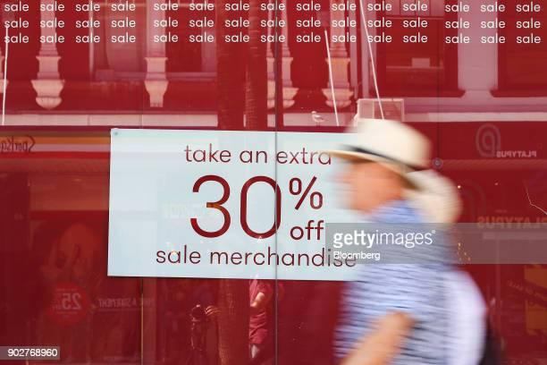 Pedestrians walk past a sale sign displayed in a store window in the Manly Corso retail area in Sydney Australia on Friday Jan 5 2018 The Australian...