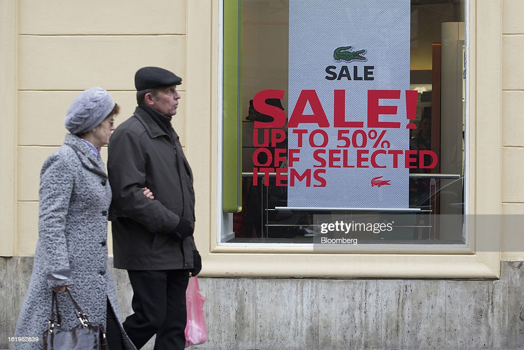 Pedestrians walk past a sale sign in the window of a Lacoste SA retail store in Prague, Czech Republic, on Sunday, Feb. 17, 2013. Worsened outlook for Czech economy is in line with the government's expectations and lower-than-planned tax revenue is 'manageable' under 2013 budget, Prime Minister Petr Necas said on Czech public television. Photographer: Martin Divisek/Bloomberg via Getty Images