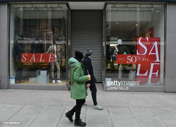 Pedestrians walk past a shuttered and closed-down branch of a Moss Bros clothes store on Oxford Street in central London on March 24, 2021. -...