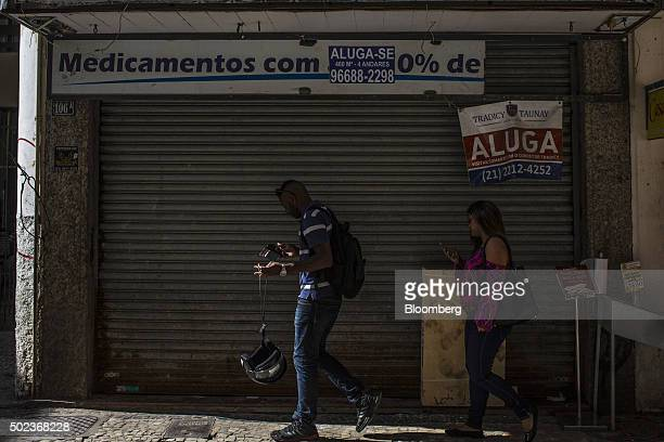 Pedestrians walk past a shuttered business in downtown Rio de Janeiro Brazil on Monday Dec 21 2015 Brazil has slipped deeper into recession with...