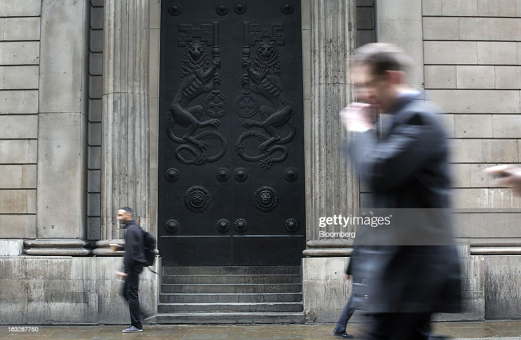 Pedestrians walk past a side entrance to the Bank of England (BoE) in London, U.K., on Thursday, March 7, 2013. The pound dropped to its weakest level in more than 2 1/2 years versus the dollar before Bank of England policy makers announce their decision on whether they will add more stimulus to boost the U.K. economy. Photographer: Simon Dawson/Bloomberg via Getty Images