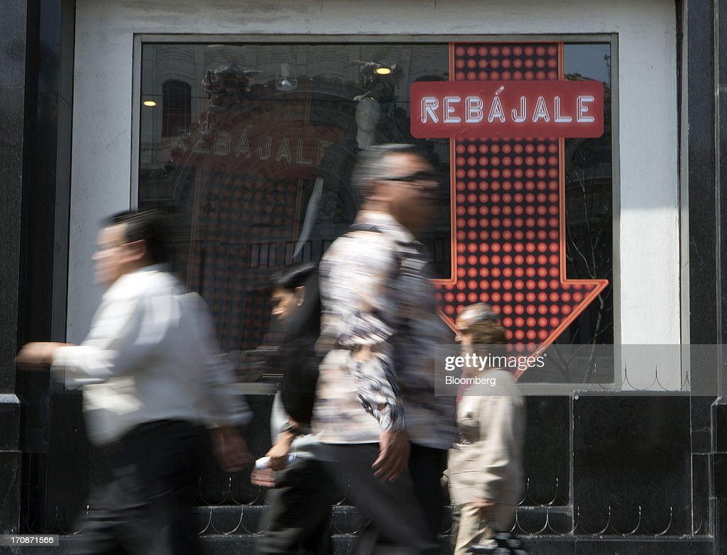 Pedestrians walk past a sign advertising low prices at a Sears store in Mexico City, Mexico, on Wednesday, June 19, 2013. Monthly retail sales figures for Mexico are expected to be reported on June 20. Photographer: Susana Gonzalez/Bloomberg via Getty Images