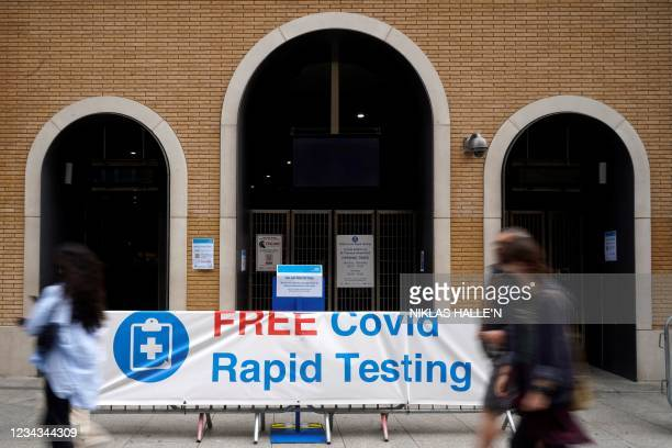 """Pedestrians walk past a sign advising members of the public of a """"Free Covid-19 Testing"""" site in south London, on July 31, 2021. - Coronavirus case..."""