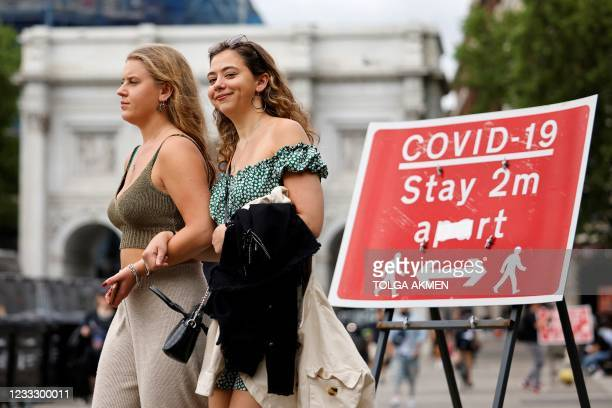 Pedestrians walk past a sign asking people to social distance, near Marble Arch in central London on June 6, 2021. - The Delta variant of the...