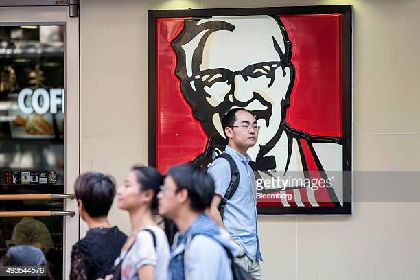 Pedestrians walk past a sign depicting Colonel Harland Sanders the founder of Kentucky Fried Chicken outside a Yum Brands Inc KFC restaurant in...