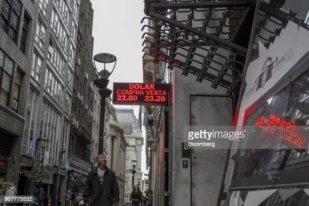 Pedestrians walk past a sign displaying the US dollar exchange rate outside of a currency exchange house in Buenos Aires Argentina on Thursday May 10...