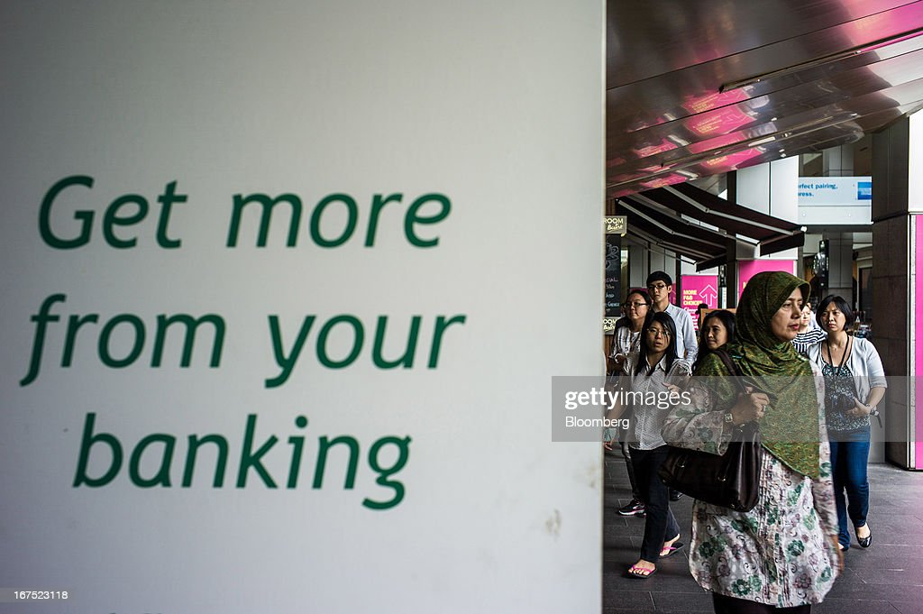 Pedestrians walk past a sign for banking in Kuala Lumpur, Malaysia, on Thursday, April 25, 2013. Malaysians will go to the polls on May 5. Prime Minister Najib Razak's National Front coalition is seeking to extend its 55 years of unbroken rule in the face of a resurgent opposition led by Anwar Ibrahim. Photographer: Sanjit Das/Bloomberg via Getty Images