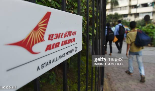 Pedestrians walk past a sign of state carrier Air India outside its headquarters in Mumbai on January 10 2018 Indian lawmakers cleared a proposal in...