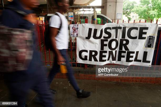 Pedestrians walk past a sign that reads 'Justice For Grenfell' The charred remains of clading are pictured on the outer walls of the burnt out shell...