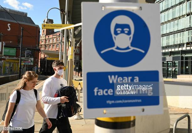 Pedestrians walk past a sign urging people to 'wear a face covering' due to the COVID-19 pandemic, in Manchester, northwest England on August 3...