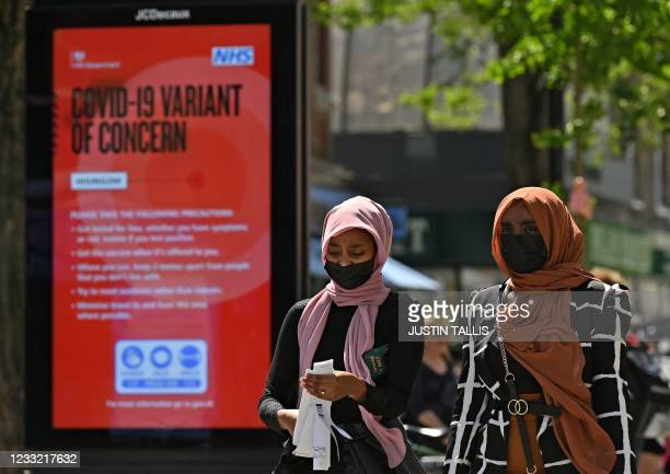 """Pedestrians walk past a sign warning members of the public about a """"Coronavirus variant of concern' is pictured in Hounslow, west London on June 1,..."""