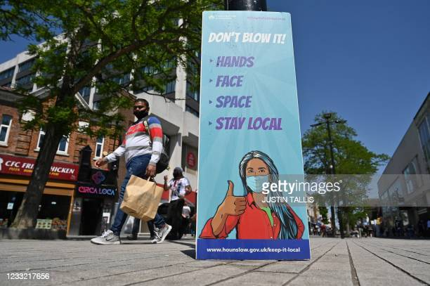 Pedestrians walk past a sign warning members of the public about the spread of Coronavirus, as they walk along the street in Hounslow, west London on...