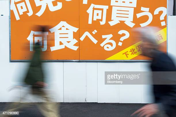 Pedestrians walk past a sign with Japanese characters that reads 'What to buy What to eat What to see' in the Shimokitazawa district of Tokyo on...