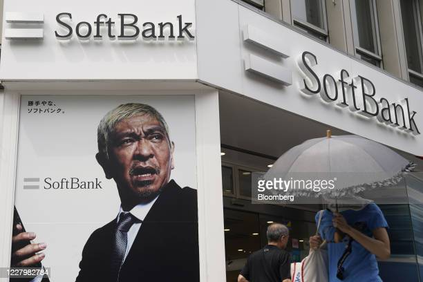 Pedestrians walk past a SoftBank Corp. Store in Tokyo, Japan, on Friday, Aug. 7, 2020. After reporting record losses in May and warning the...