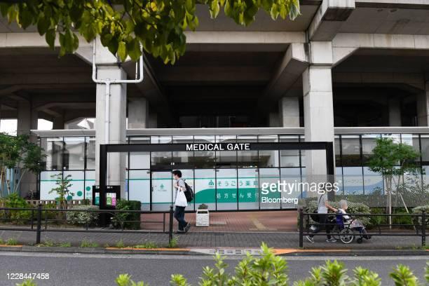 Pedestrians walk past a Sogo Medical Co. Drugstore office built under railway tracks in Tokyo, Japan, on Thursday, Sept. 3, 2020. In Tokyo, the...