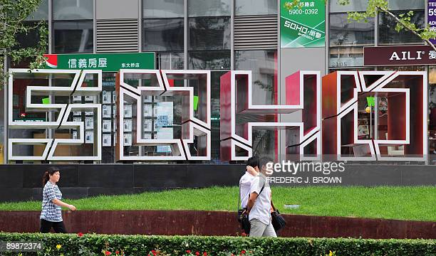 Pedestrians walk past a SOHO development in Beijing on August 19 2009 The property developer SOHO China said it has agreed to buy a top Shanghai...