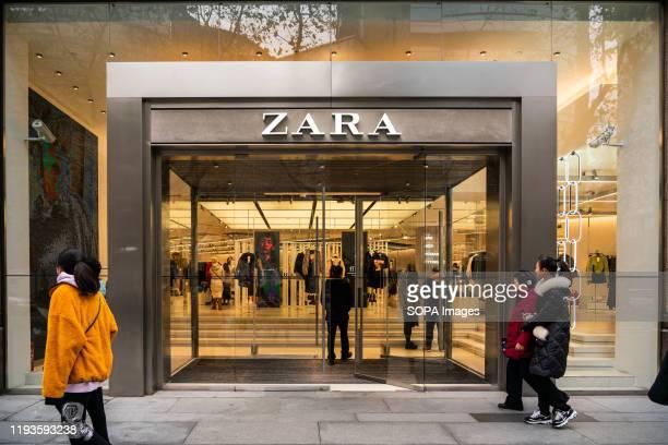 Pedestrians walk past a Spanish fast fashion retailer Zara store in Shanghai
