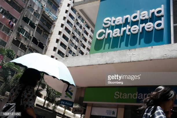 Pedestrians walk past a Standard Chartered Plc bank branch in Hong Kong China on Tuesday July 31 2018 Standard Chartered one of the biggest...