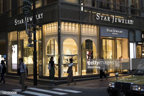 Pedestrians walk past a Star Jewelry Co store at night in the Ginza area of Tokyo Japan on Tuesday Aug 21 2018 Japan is scheduled to release...