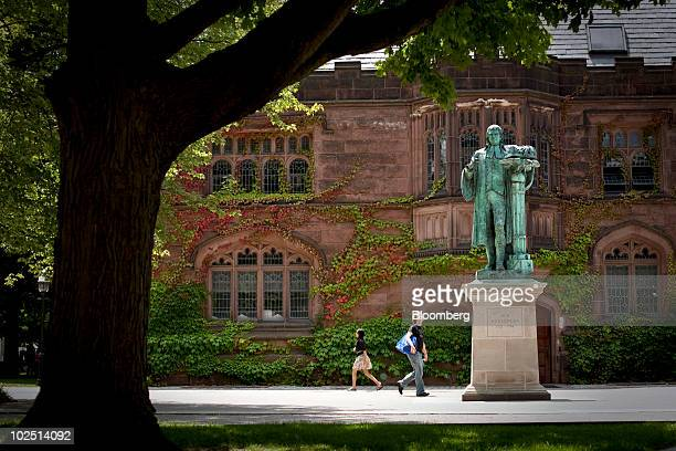 Pedestrians walk past a statue of former Princeton University president John Witherspoon near the East Pyne building on the school's campus in...
