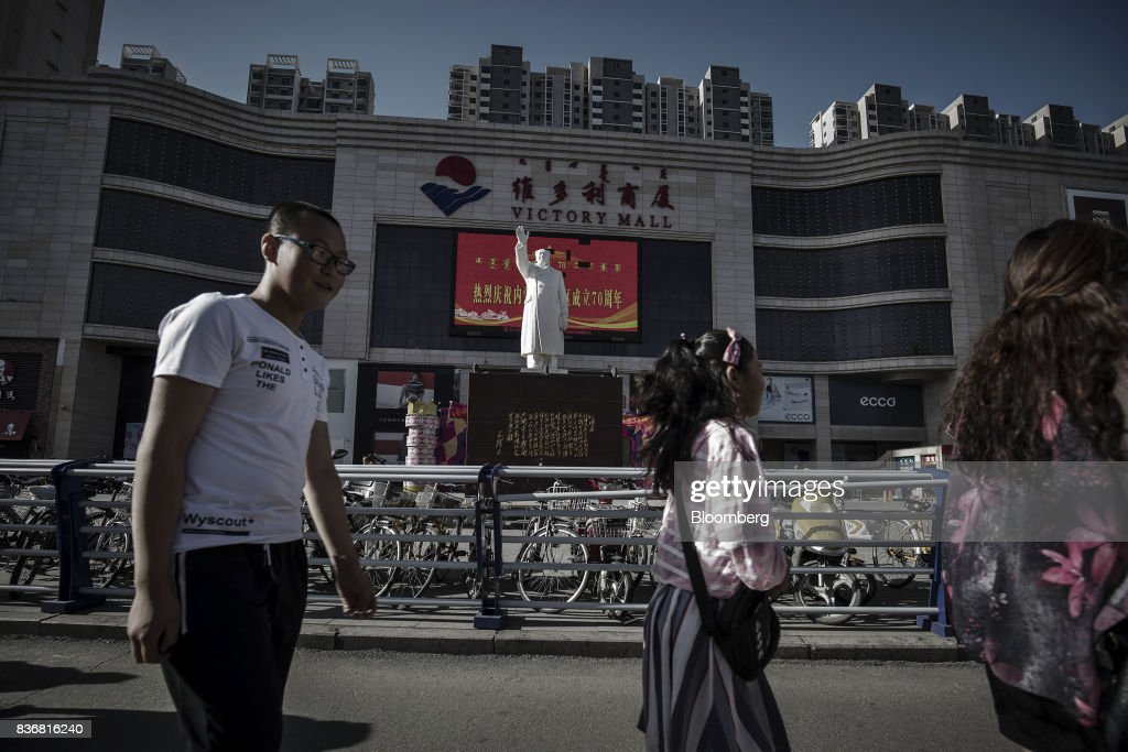 Pedestrians walk past a statue of Mao Zedong displayed in front of the Baotou Victory Shopping Mall in Baotou, Inner Mongolia, China, on Friday, Aug. 11, 2017. China's economy showed further signs of entering a second-half slowdown, as curbs on property, excess borrowing and industrial overcapacity began to bite. Photographer: Qilai Shen/Bloomberg via Getty Images