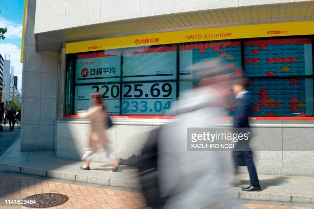Pedestrians walk past a stock indicator showing share prices of the Tokyo Stock Exchange in Tokyo on May 7 2019 Tokyo's key Nikkei stock index opened...