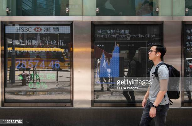 Pedestrians walk past a stocks display board showing the Hang Seng Index