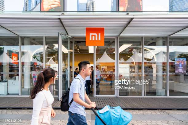 Pedestrians walk past a store of Chinese electronics company Xiaomi, in Shanghai.
