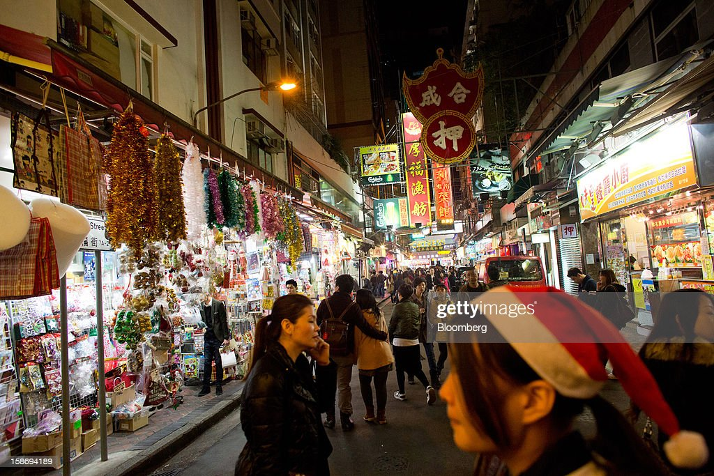 Pedestrians walk past a store selling Christmas decorations, left, in the Tsim Sha Tsui area of Hong Kong, China, on Saturday, Dec. 22, 2012. Hong Kong's economy is set for its weakest annual expansion since the global financial crisis as the European sovereign debt crisis damps global trade. Photographer: Lam Yik Fei/Bloomberg via Getty Images