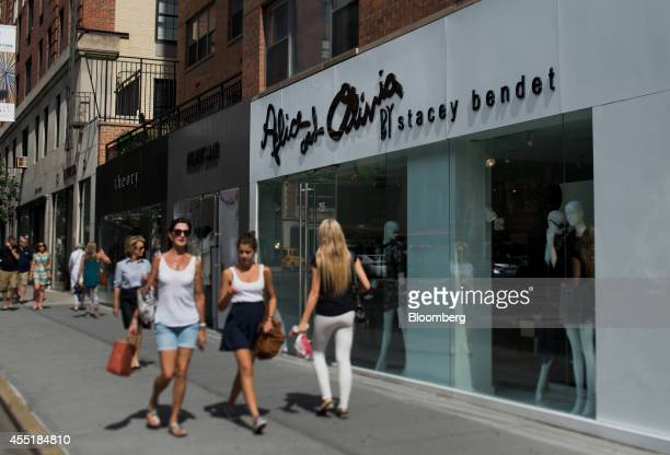 Pedestrians walk past a stores in this photo taken with a tiltshift lens on Madison Avenue in New York US on Wednesday Sept 3 2014 The Bloomberg...
