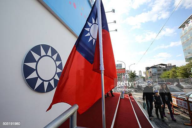 Pedestrians walk past a Taiwanese flag flying outside the headquarters of Taiwan's ruling party Kuomintang in Taipei, Taiwan, on Saturday, Jan. 16,...
