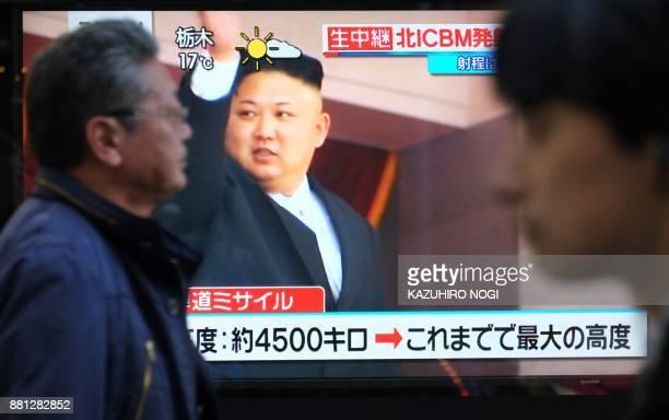 TOPSHOT Pedestrians walk past a television screen broadcasting a news report showing North Korean leader Kim JongUn in Tokyo on November 29 following...