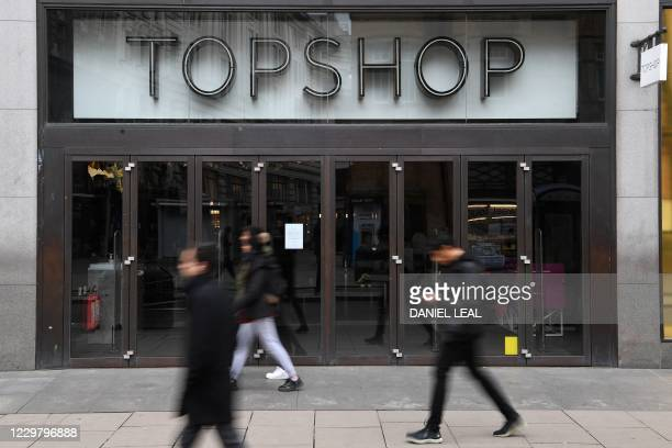 Pedestrians walk past a temporarily closed-down Topshop store on Oxford Street in London on November 26, 2020. - Britain's government on Wednesday...
