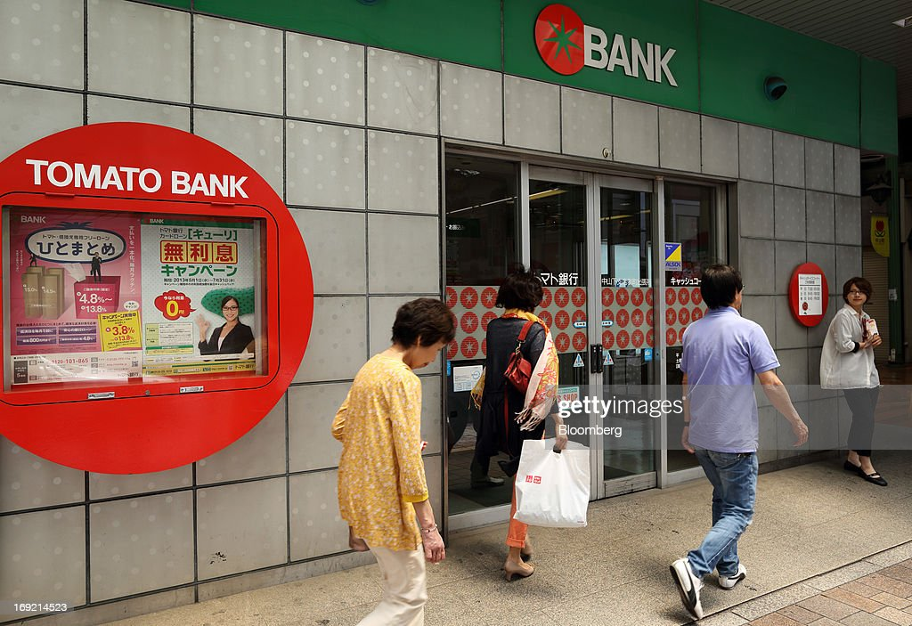 Pedestrians walk past a Tomato Bank branch in Okayama, Japan, on Tuesday, May 21, 2013. The Bank of Japan, forecast to maintain plans for expanded monetary easing at a meeting ending on May 22, is targeting 2 percent inflation in two years after more than 10 years of entrenched deflation. Photographer: Tomohiro Ohsumi/Bloomberg via Getty Images