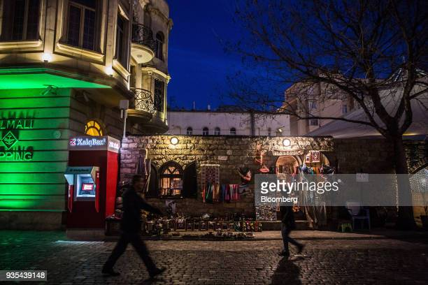 Pedestrians walk past a traditional handicraft store at night in the Old City of Baku Azerbaijan on Friday March 16 2018 Azerbaijan's economy barely...
