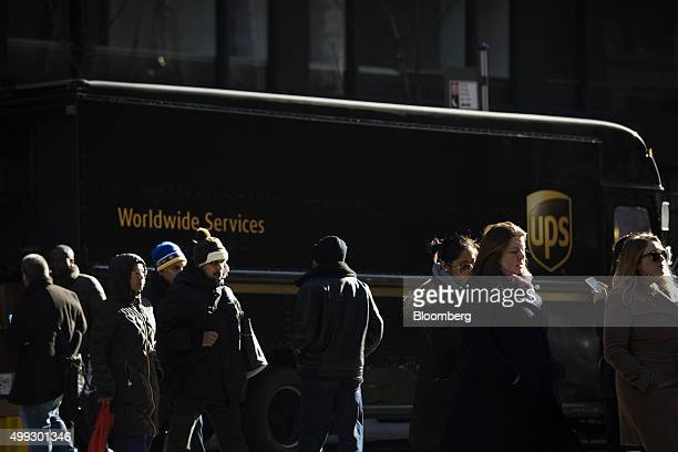 Pedestrians walk past a United Parcel Service Inc truck on Cyber Monday in New York US on Monday Nov 30 2015 Online sales on Cyber Monday may rise at...