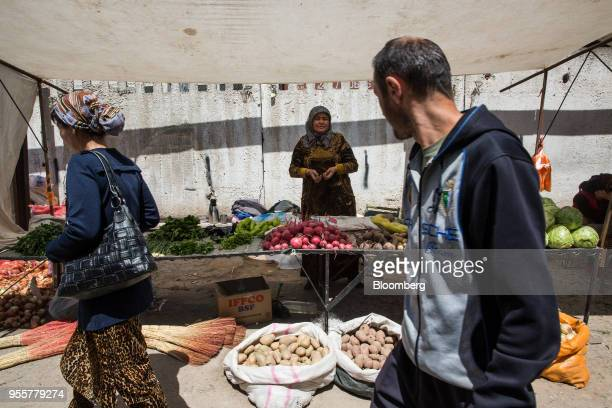 Pedestrians walk past a vegetable stall at a market in Dushanbe Tajikistan on Sunday April 22 2018 Flung into independence after the Soviet Union...