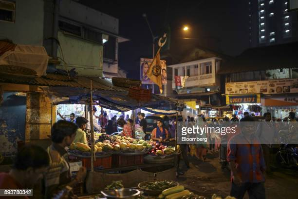 Pedestrians walk past a vegetable stall in Mumbai India on Friday Dec 15 2017 India's inflation surged past the central bank's target bolstering a...