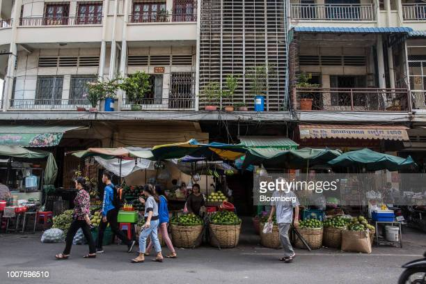 Pedestrians walk past a vendor selling green oranges at a stall at Orussey Market in Phnom Penh Cambodia on Friday July 27 2018 Cambodian Prime...