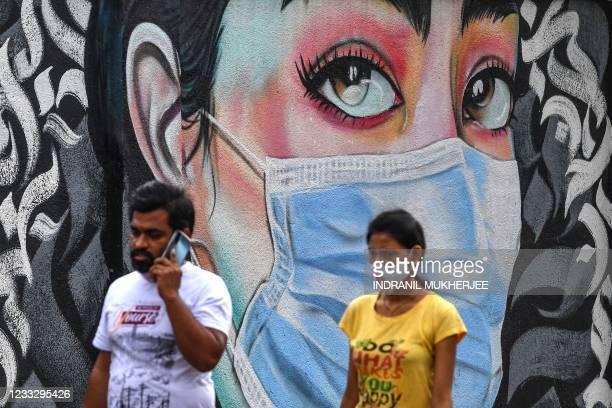 Pedestrians walk past a wall mural representing awareness measures against the Covid-19 coronavirus, in Navi Mumbai on June 6, 2021.