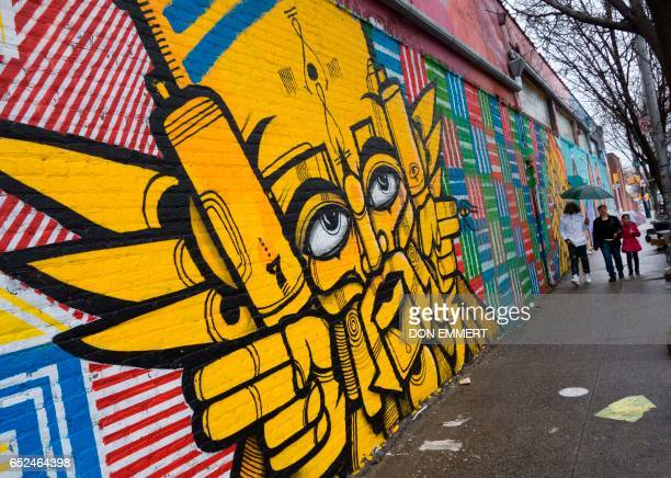 Pedestrians walk past a wall outside The Point in the Bronx on March 7 2017 in New York Rappers graffiti artists dancers DJs in the early 1970s...