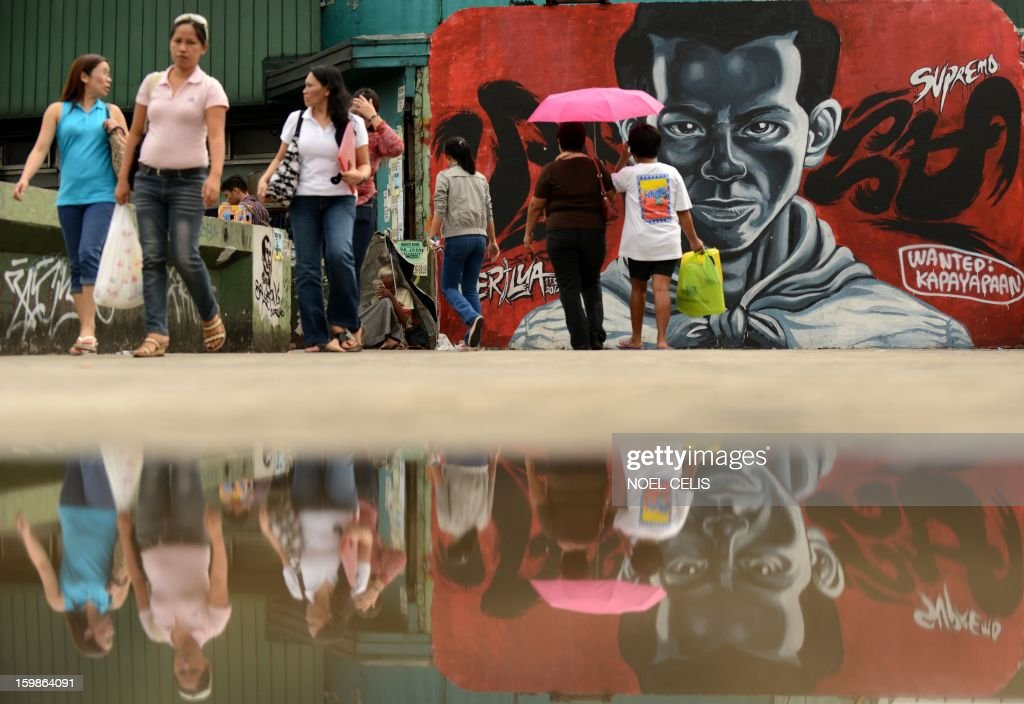 Pedestrians walk past a wall painted with a street art featuring Philippine working class hero Andres Bonifacio at an overpass in Manila on January 22, 2013. Andres Bonifacio led Katipuneros in 1896 to a failed war of independence against Spain's colonial rulers.