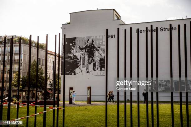 Pedestrians walk past a wall with illustrations in memory of the evaders at a memorial to the Berlin Wall in Bernauer Strasse on August 13 2019 in...