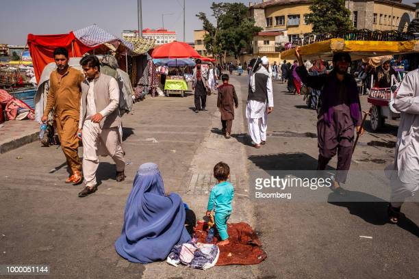Pedestrians walk past a woman sitting with a child on the road in Kabul Afghanistan on Thursday July 12 2018 US President Donald last year said 16000...