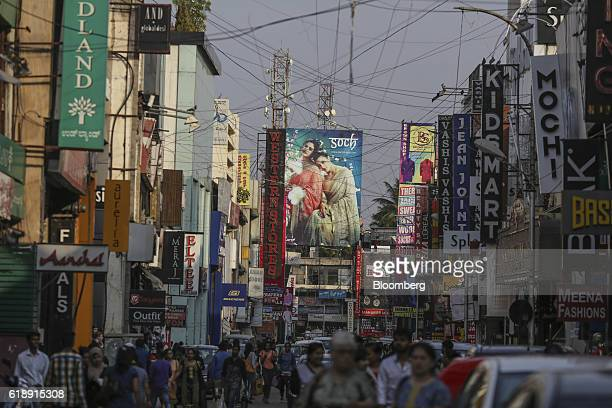 Pedestrians walk past advertisements and signage hanging along a commercial street in Bangalore India on Thursday Oct 27 2016 India will soon have a...