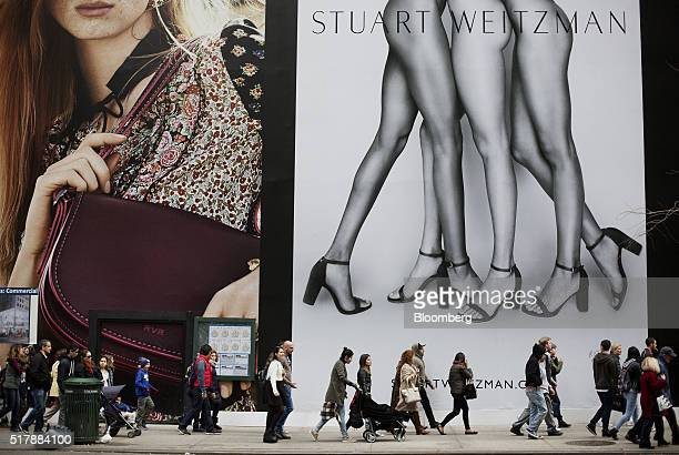 Pedestrians walk past advertisements on Fifth Avenue in New York US on Thursday March 24 2016 The Conference Board is scheduled to release consumer...